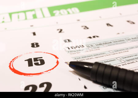 2019 calendar with 1040 income tax form for 2018 showing tax day for filing on April 15 - Stock Photo