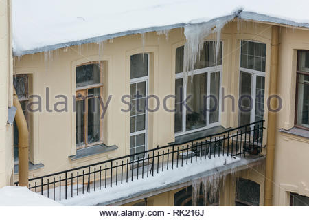 Photo of big icicles hanging from building, many people get injured by the drop of icicles/ poor attic insulation, danger for humans. - Stock Photo
