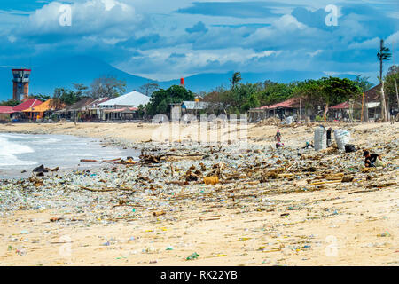 Pollution of plastic bottles, cups, straws and other litter washing up on the beach at Jimbaran Bay, Bali Indonesia. - Stock Photo