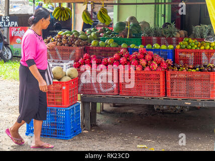 Female shopkeeper in front of fruit grocery store with variety of fruits for sale in Jimbaran, Bali Indonesia. - Stock Photo