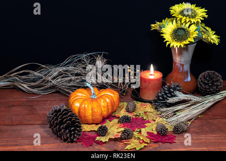Silk maple leaves, beautiful bouquet of sunflowers, frosted pinecones and orange candle on tabletop with dark background. - Stock Photo
