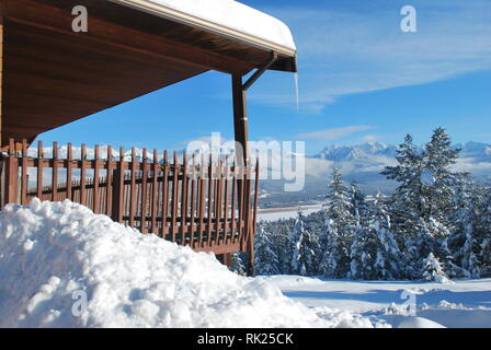 Snow piled beside the deck of a house overlooking Lake Windermere, British Columbia - Stock Photo