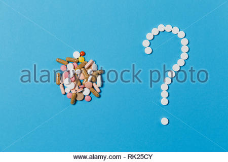 Medication white round tablets arranged in question mark shape isolated on blue color background. Bunch of multicolored pills, colorful sign. Concept  - Stock Photo