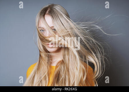 blond young woman with long windswept tousled hair blowing into her face - Stock Photo