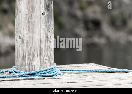 Blue rope wrapped around wooden bollard, close up, cropped - Stock Photo