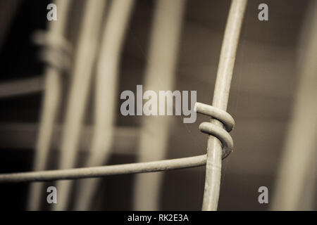 Abstract detail of metal wires connected by hook. Sad melancholy background in brown tone. Old wire mesh close-up. Idea of connection and cohesion. - Stock Photo