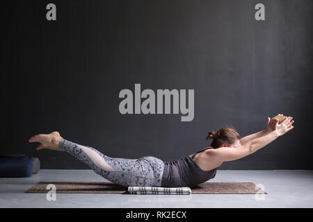 woman in a yoga position salabhasanathe sea in
