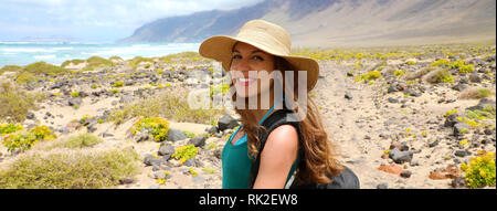 Happy beautiful traveler girl with straw hat looking to the camera. Young female backpacker exploring Lanzarote, Canary Islands. Banner panorama. - Stock Photo