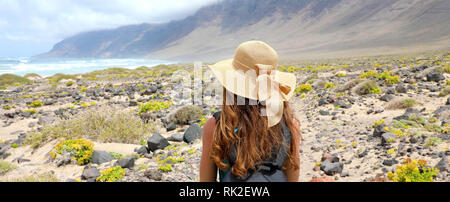 Rear view of traveler girl with straw hat looking at beautiful natural landscape. Young female backpacker exploring Lanzarote, Canary Islands. Banner  - Stock Photo