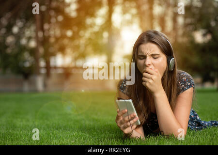 Woman teenager girl yawning bored with on line content holding a mobile phone outdoors lying down on green lawn headphones on head. Multicultural mode - Stock Photo