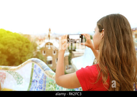 Back view of woman taking picture of Park Guell and landscape from terrace of the park, Barcelona, Spain - Stock Photo