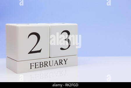 February 23st. Day 23 of month, daily calendar on white table with reflection, with light blue background. Winter time, empty space for text - Stock Photo