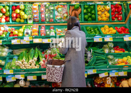 pretty unidentified women shopping vegetables and fruits in supermarket