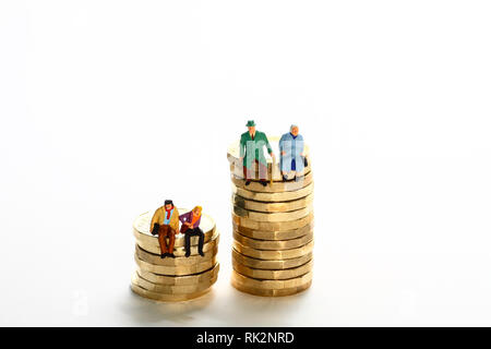 Conceptual diorama image of a miniture figure retired couple and young couple sat on a stack of pound coins - Stock Photo