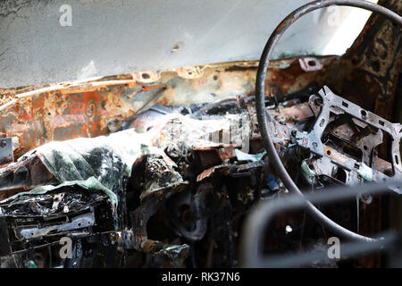 inside of burnt out wreckage of stolen car. Crime scene image of vehicle interior ruined by fire or arson. molten plastic and metal and steering wheel - Stock Photo