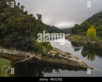 Confluence of Ahuahu Stream with Whanganui River, native forest bush clad hills, calm still autumn morning, Te Tuhi Landing, North Island, New Zealand - Stock Photo