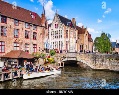 25 September 2018: Bruges, Belgium - Tourists boarding a tour boat on the canal by the Wollestraat Bridge in Bruges. - Stock Photo