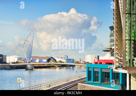 2 November 2018: Salford Quays, Manchester, UK - Media City Footbridge, and a large white cloud behind it. - Stock Photo