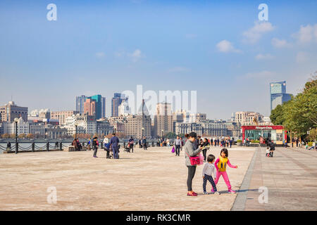 1 December 2018: Shanghai, China - Visitors on the bank of the Huangpu River on the Pudong side, opposite The Bund, Shanghai. - Stock Photo