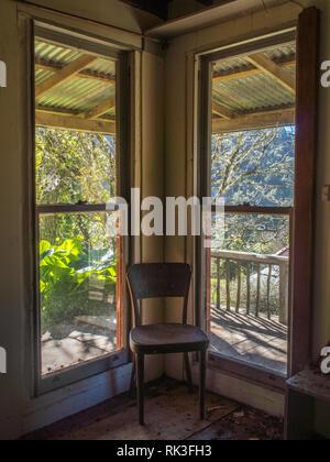 Empty chair in the corner by the windows, sunshine on the verandah, abandoned house, Ahu Ahu Ohu, Whanganui River, New Zealand - Stock Photo
