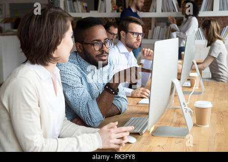 Serious african office worker explaining coworker new online project - Stock Photo