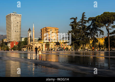 Young family and other locals at Skanderbeg Square in front of the Skanderbeg statue, Et'hem Bey Mosque and a Hotel, Tirana, Albania - Stock Photo