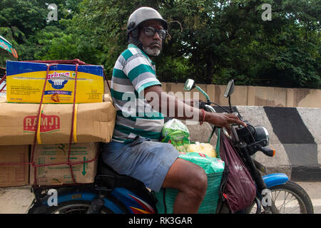 A man with goggles and his shopping on the back of his motorbike in Chennai, Southern India - Stock Photo