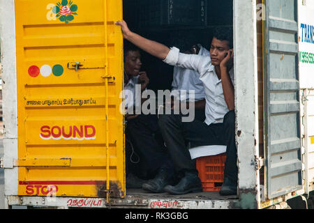 Sitting on a crate in the back of a van on the way to work - Chennai, southern India - Stock Photo