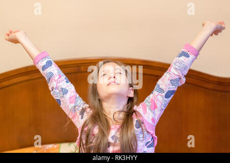A nice child girl enjoys sunny morning. Good morning at home. Child girl wakes up from sleep. Little girl stretching in bed at home. Time to sleep. - Stock Photo