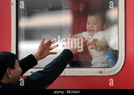 Beijing, China. 26th Jan, 2013. File photo taken on Jan. 26, 2013 shows a man making a hugging gesture to his grandson from outside the train window at the railway station in Hangzhou, east China's Zhejiang Province. Platforms, witnessing memorable moments of joy and sadness, are the epitome of each year's Spring Festival travel rush, during which hundreds of millions of Chinese go back to their hometowns for family gatherings. Credit: Ju Huanzong/Xinhua/Alamy Live News - Stock Photo