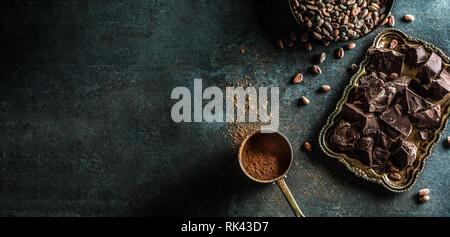 Dark chokolate cocoa beans and powder on concrete table - Stock Photo