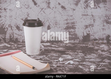Working on the go. Coffee cup and notepad on grey stone table. Copy space - Stock Photo