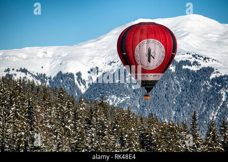 A hot air balloon floats above trees in the French alpine resort of Courchevel. - Stock Photo