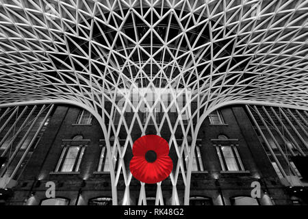 The huge poppy at Kings Cross Railway Station on Armistice Day in London City, England, UK - Stock Photo