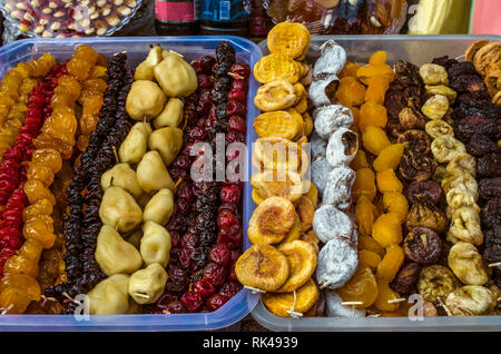 Candied fruits,pears,figs, prunes, apricots, peaches  and various cherries in plastic trays - Stock Photo