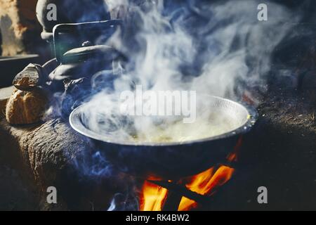 Preparation rice and curry meal. Cooking on fire pit in traditional home kitchen in Sri Lanka. - Stock Photo
