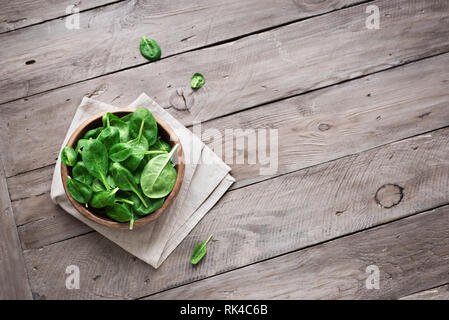 Green baby spinach leaves in bowl on wooden background, top view, copy space. Clean eating, detox, diet food ingredient - green organic spinach. - Stock Photo