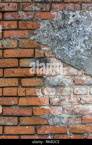 Detailed view of a older orange brick masonry wall with cement plaster to fall from the wall, Portugal - Stock Photo