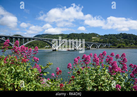 Patterson Bridge on the Rogue River, with a jet boat passing under; from Jot's Resort in Gold Beach on the southern Oregon coast. - Stock Photo