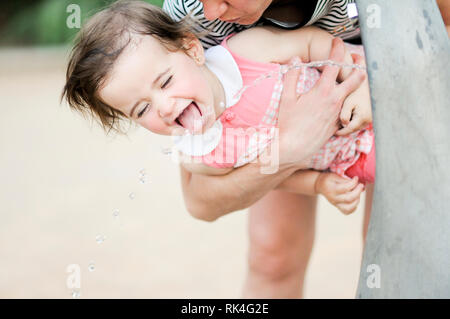 Little girl drinking water in a park fountain - Stock Photo