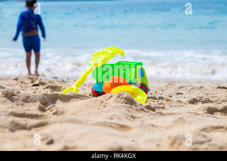 Children's beach toys - buckets, spade, machine, car and shovel on sand on a sunny day. Silhouette of a boy. - Stock Photo