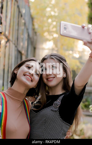 Two beautiful girls taking selfie on the phone in the autumn park - Stock Photo