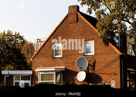 Satellites attached to suburban brick home on a beautiful afternoon. - Stock Photo