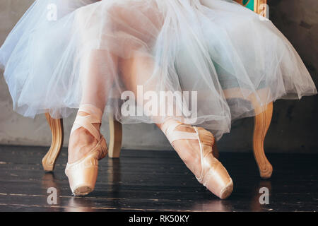 The ballerina ballet dancer in tutu skirt and pointe shous sitting on the classic chair - Stock Photo