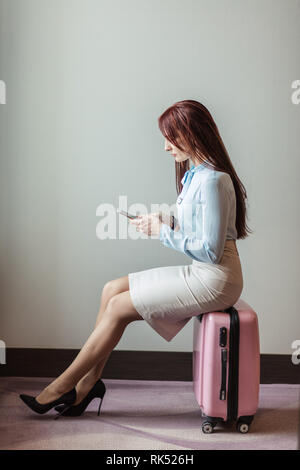 Profile of a cute business woman dressed in formal manner, sitting on a pink baggage bag, making a phone call against grey background - Stock Photo