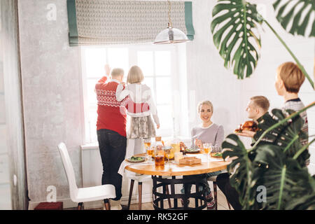 old man and little girl are looking at the window while other members of family having dinner, back view photo - Stock Photo