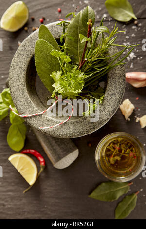 Fresh mixed herb bouquet garni in a stone pestle and mortar with oil, spices and lemon on a rustic table - Stock Photo