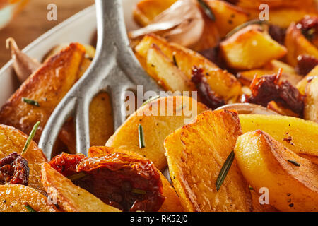 Pan fried rosemary potato wedges with an old metal spatula in a close up full frame view - Stock Photo