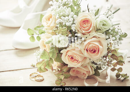 Marriage day setting with bridal bouquet of pink roses, white brides shoes and wedding rings sitting on wooden surface, viewed in close-up - Stock Photo