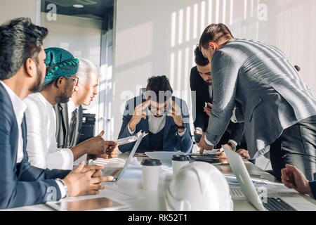 Conflict on business meeting with team. Young male Chief Executive feeling tired, stressed and exhausted during stressful business negotiations with i - Stock Photo